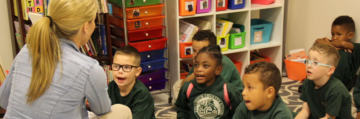 Elementary students listening to their teacher read a story.